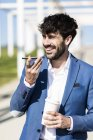 Businessman holding smartphone and takeaway coffee — Stock Photo