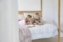 Girl lying on bed with grandmother — Stock Photo