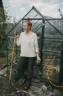 Woman standing in front of greenhouse — Stock Photo