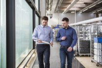 Men talking about product in factory — Stock Photo