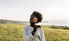 Woman covering eye with lollipop — Stock Photo