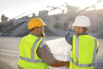 Quarry workers checking site plan — Stock Photo
