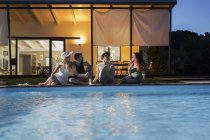 Friends relaxing at the poolside — Stock Photo