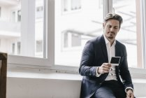 Businessman looking at instant photo — Stock Photo