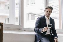 Homme d'affaires regardant la photo instantanée — Photo de stock