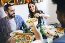 Friends having French fries and pizza — Stock Photo