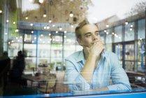 Человек, сидящий в кафе и смотрящий в окно — стоковое фото