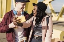 Пара ходить по мосту и делать селфи — стоковое фото