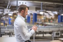 Man in factory looking at cell phone — Stock Photo