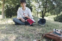 Young man sitting on meadow in park using a fidget spinner — Stock Photo