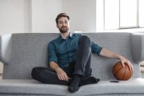 Man sitting on couch with basketball — Stock Photo