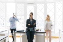 Жінка в офісі запуску з колегами — стокове фото
