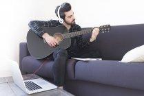 Uomo in cuffia suonare la chitarra — Foto stock