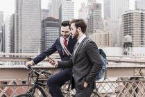 США, Нью-Йорк, Бруклинский мост, два бизнесмена, прогуливающиеся по городу на велосипеде и смартфоне — стоковое фото