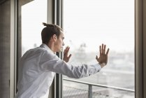 Porträt eines jungen Geschäftsmannes, der am Fenster steht — Stockfoto