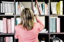 Задній вид бізнес-леді на книжковій полиці — стокове фото