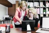 Dos empresarias con laptop en el escritorio en la oficina - foto de stock