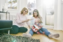 Grandmother, mother and baby girl sitting on floor playing drums — Stock Photo