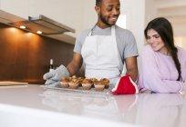 Обрезанный портрет молодой пары с кексами на подносе на кухне — стоковое фото