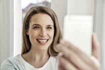 Щасливі жінка бере на selfie в домашніх умовах — стокове фото