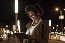 Young woman with tablet and headphones waiting at the tram stop — Stock Photo