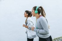 Two women running in the street, one with headphones — Stock Photo