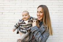 Ritratto di giovane donna che tiene bambino ragazzo — Foto stock