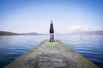 Frau praktizieren Yoga macht einen Kopfstand auf einem Steg am See — Stockfoto