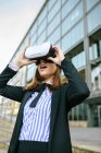Businesswoman using VR goggles in city — Stock Photo
