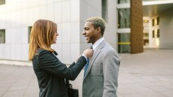 Young businesswoman fastening tie of businessman — Stock Photo