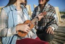 Zwei Frauen am Strand mit Ukulele in Spanien, Andalusien, vejer de la frontera — Stockfoto
