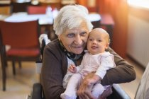 Old smiling woman holding great-granddaughter — Stock Photo