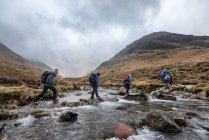 Непал, Гімалаї, Кхумбу, Еверест регіон. Мандрівників, перетинаючи гірській річці — стокове фото
