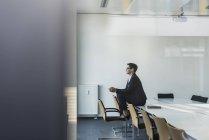 Porträt einer reifen Geschäftsfrau, die im Konferenzraum auf einem Tisch sitzt — Stockfoto
