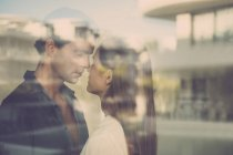 Couple standing by the windowpane — Stock Photo