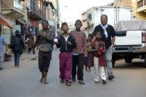 Madagascar, Fianarantsoa, Social worker walking on street with a group of teenage street boys — Stock Photo