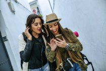 Young female travelers watching photos in a camera on street — Stock Photo