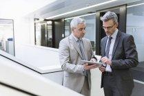 Geschäftsleute, die mit digitalen tablet — Stockfoto