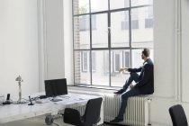 Молодой предприниматель, глядя из окна в офисе — стоковое фото