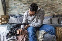 Portrait recadré d'homme caressant chien noir — Photo de stock