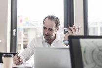 Retrato de empresário maduro segurando smartphone e tomar notas — Fotografia de Stock