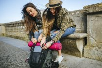 Travelling women packing backpack on street — Stock Photo