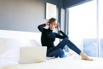 Woman sitting on bed with laptop — Stock Photo