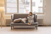Mulher sentada no sofá e olhando para o lado — Fotografia de Stock