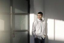 Молодою людиною, в окулярах, стоячи з руки в кишені в офісі — стокове фото