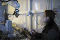 Man looking at robot arm in a sensor technology plant — Stock Photo