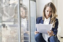 Businesswoman sitting on window sill in office and reading papers — Stock Photo
