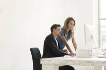 Young man and woman working together in office — Stock Photo