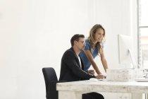 Молодий чоловік і жінка, які працюють разом в офісі — стокове фото