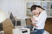 Vista lateral de la madre autónoma abrazando al bebé en la honda en la oficina en casa - foto de stock